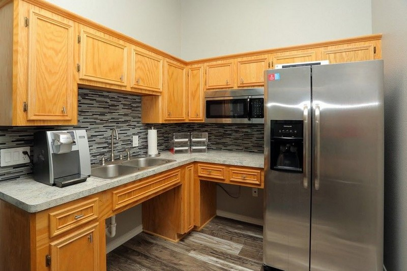 Apartment kitchen with stainless steel refrigerator and wood color cabinets.