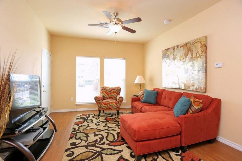 Apartment living room with red couches and ceiling fan