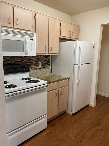 Apartment kitchen with light color cabinets and white appliances