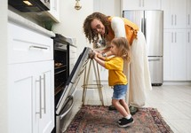 Woman and child closing oven door