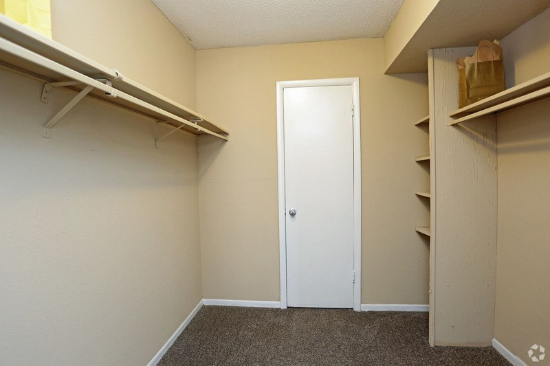 Walk in closet with clothes rods and shelves