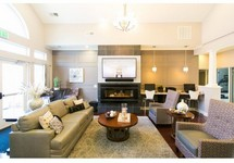 Interior of clubhouse, couches, chairs, fireplace, lots of windows