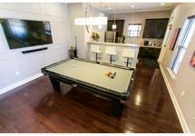 Pool table on hardwood floor near kitchen area, flatscreen TV on the wall