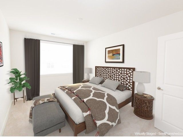 Large bedroom with neutral colored bedding, large window