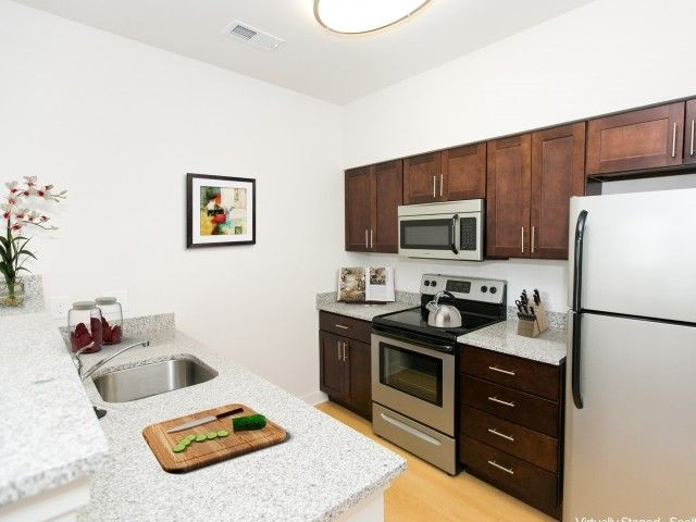 kitchen with medium stained wood cabinets, light granite countertops and stainless steel appliances
