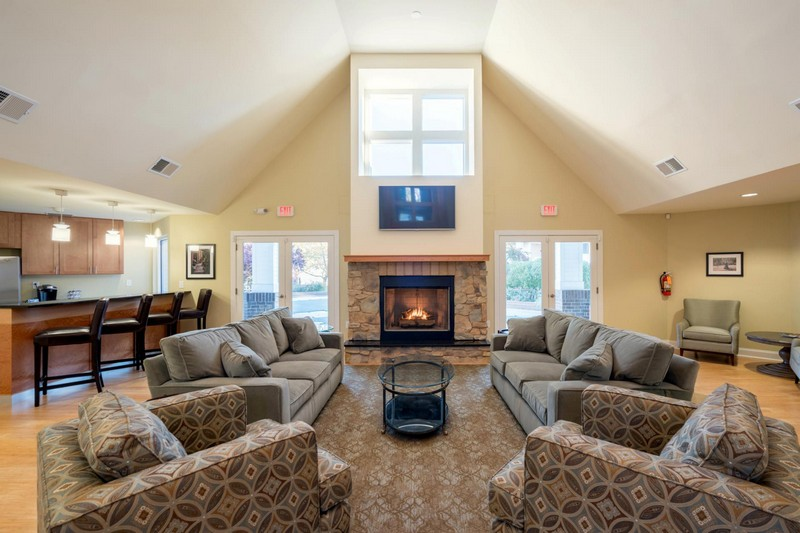 Interior of clubhouse with couches, kitchen, fireplace and windows