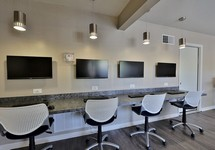 long counter with monitors and stools