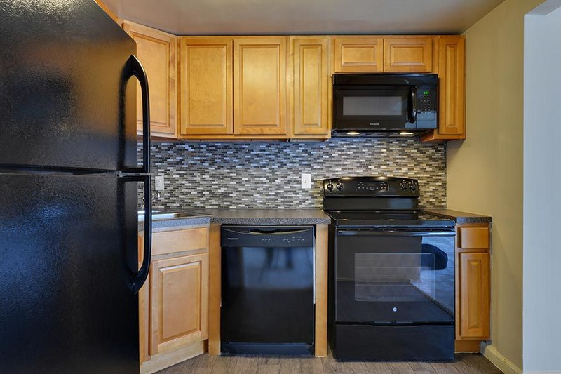 kitchen with brown cabinets, backsplash, black appliances