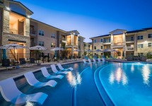 Resort style swimming pool with sundeck and chairs