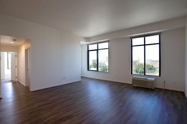 Apartment living area with two large windows and hardwood floors. Click to view the photo gallery.