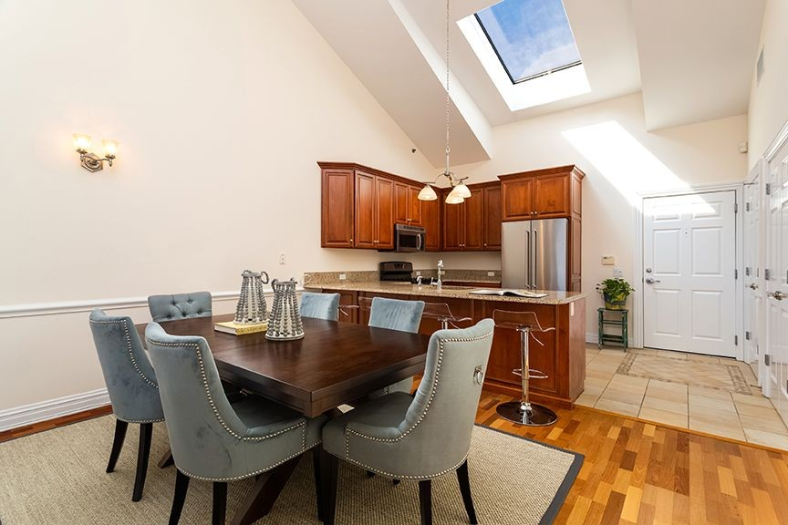 Dining area and kitchen with stainless steel appliances, high ceilings and skylight
