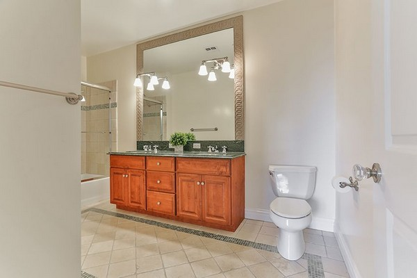 Bathroom with dual sinks, dark marble counter, tumbled marble floors and custom cherry wood cabinets. Click to view the photo gallery.