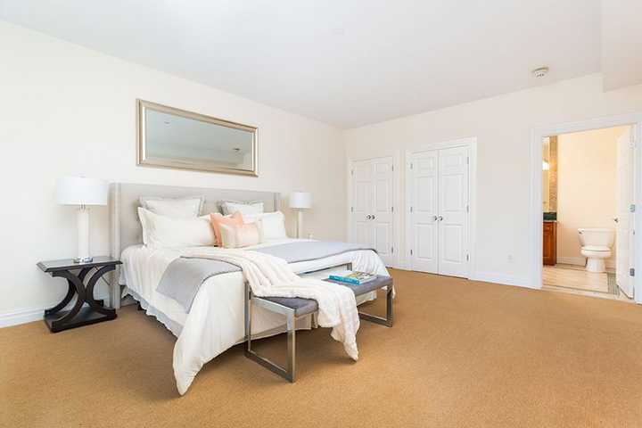 Master bedroom with tan carpet leading to bathroom. Click to view the full size image.