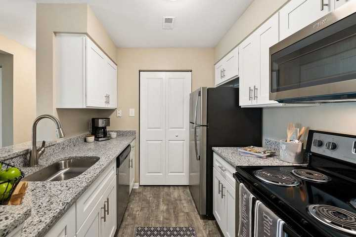 kitchen with white cabinets and grey wood look flooring. Click to view the full size image.