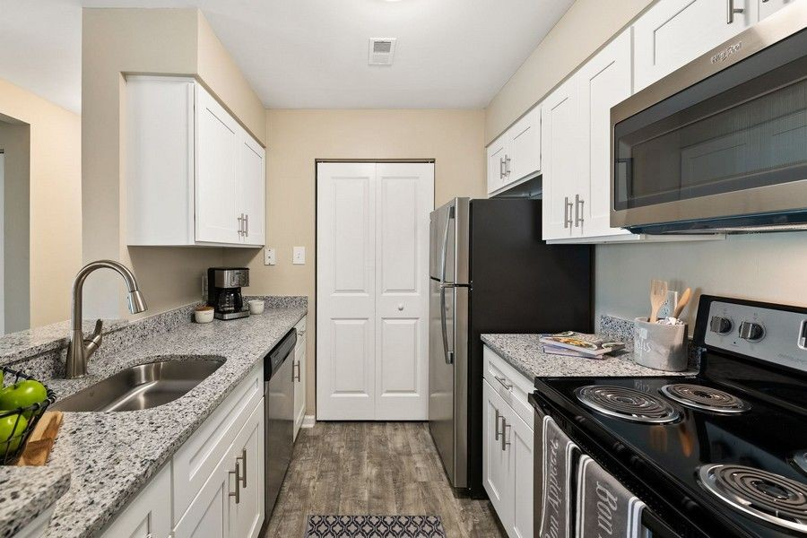 kitchen with white cabinets and grey wood look flooring