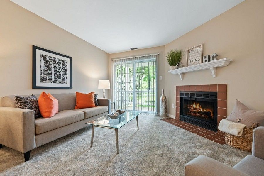 living room with grey carpet, fireplace, large windows