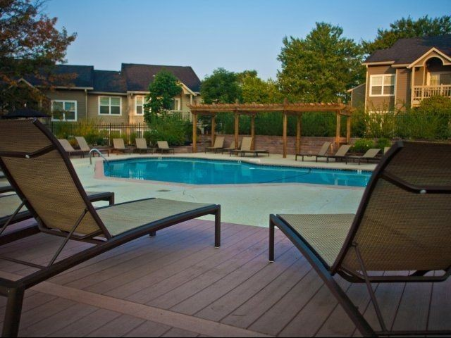 2 chairs looking out to pool, across from pergola