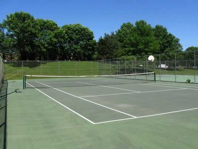 outdoor tennis courts surrounded by trees and grass. Click to view the full size image.