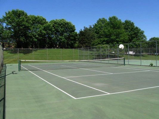 outdoor tennis courts surrounded by trees and grass. Click to view the photo gallery.