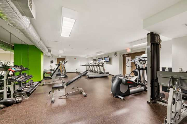 Fitness center with cardio equipment and free weights. Click to view the full size image.
