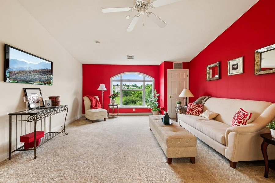 Large carpeted living room with couch, footrest, TV, and picture window