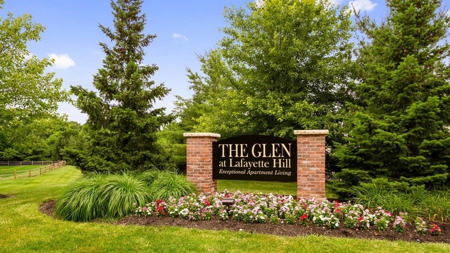 Property sign with trees and flowers