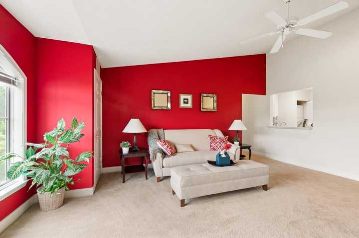 Apartment living room with carpet, white furniture, sloped ceiling and red wall. Click to view the full size image.