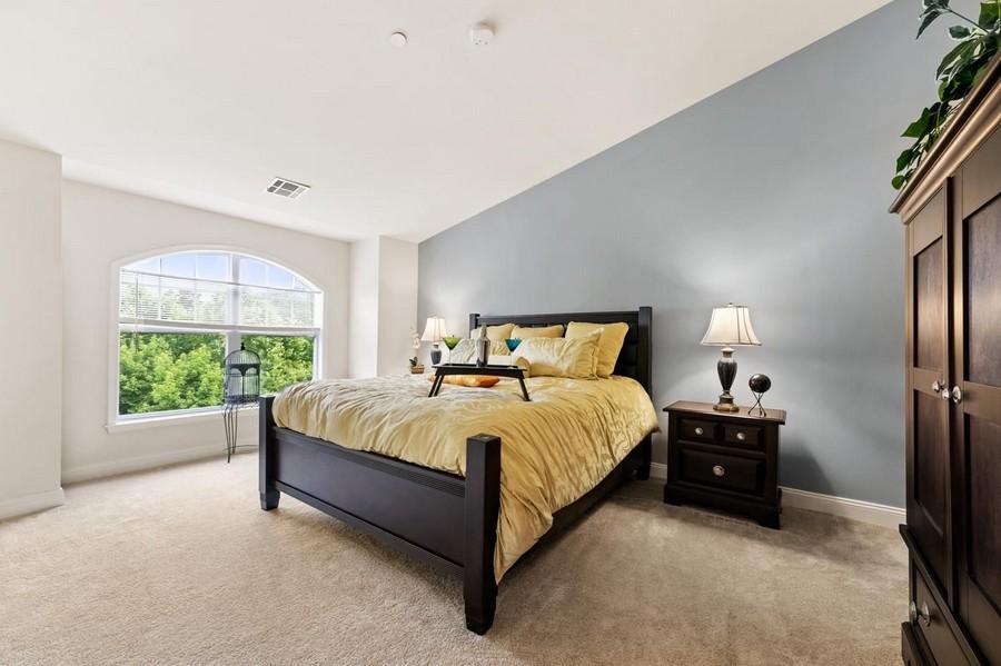 Apartment bedroom with dark wood furniture and plush carpet