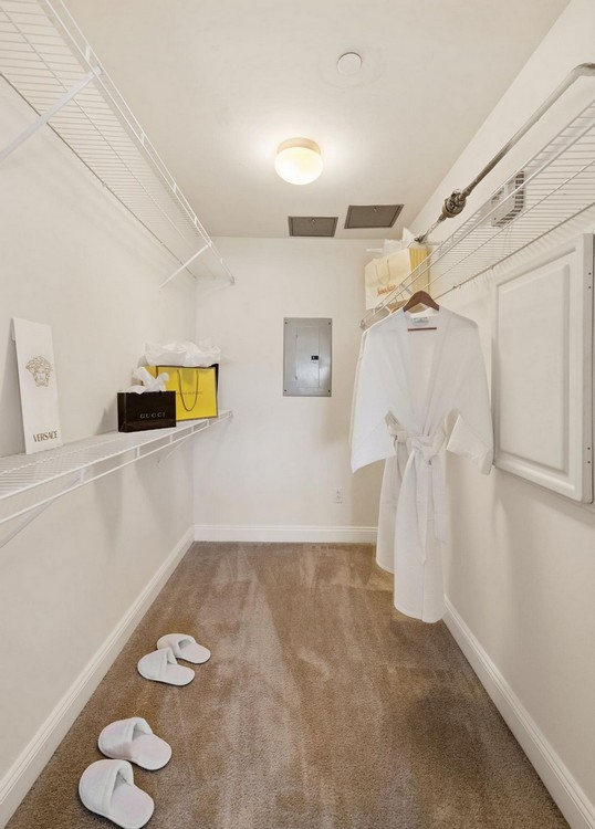 Walk-in closet containing racks and shelves, with slippers and bathrobes