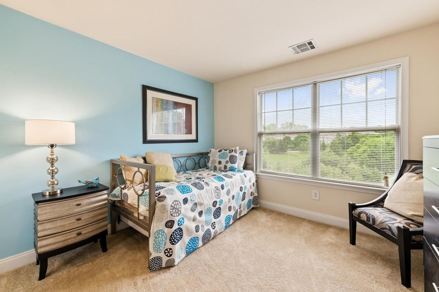 Second bedroom with daybed and chair in front of large window