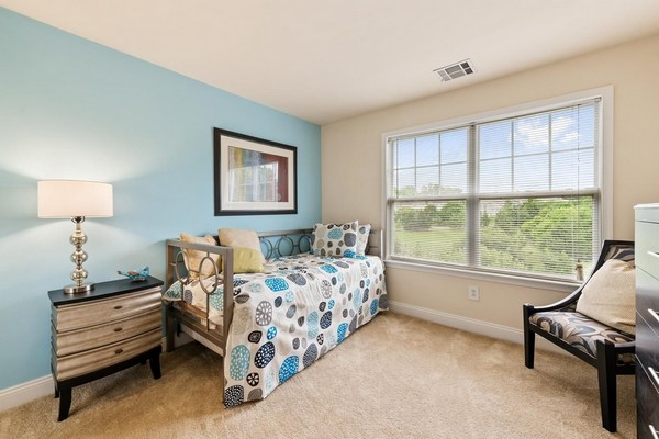 Second bedroom with daybed and chair in front of large window. Click to view the photo gallery.