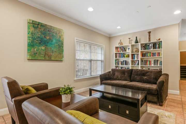 Clubhouse seating area with chairs, coffee table, couch, and bookshelf. Click to view the full size image.