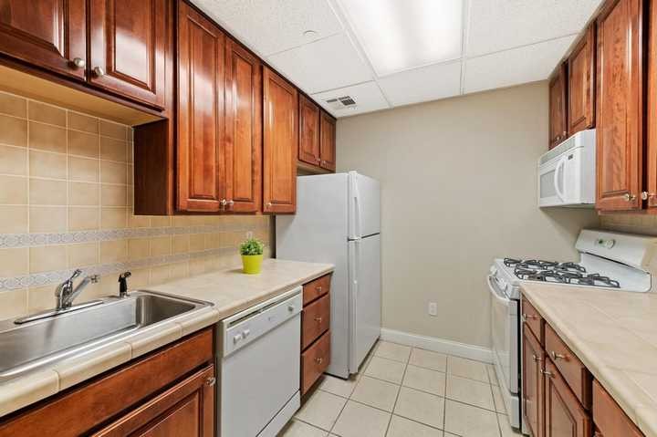 Apartment kitchen with white appliances and tile floor. Click to view the full size image.