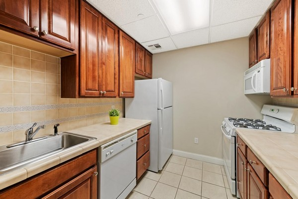 Apartment kitchen with white appliances and tile floor. Click to view the photo gallery.