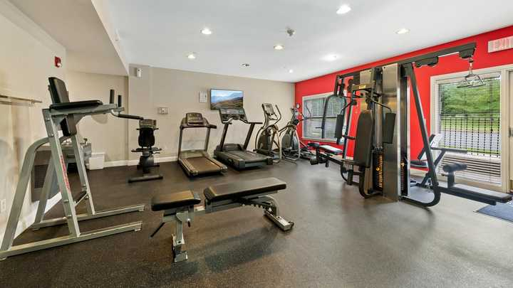 Weight bench and strength training machine in fitness center. Click to view the full size image.