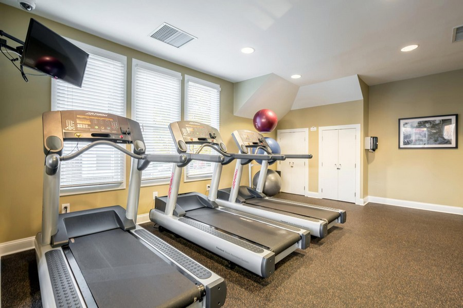 fitness center with treadmills, television and windows