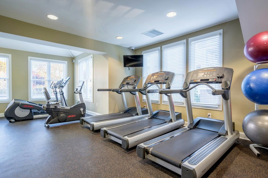 fitness center with work out equipment and fitness balls