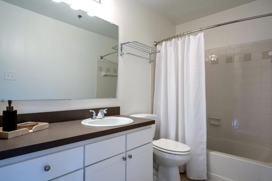 bathroom with long vanity, mirror, toilet and bathtub