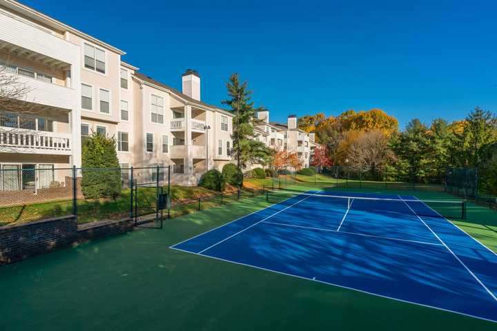 blue tennis courts, next to building, surrounded by trees, grass. Click to view the full size image.