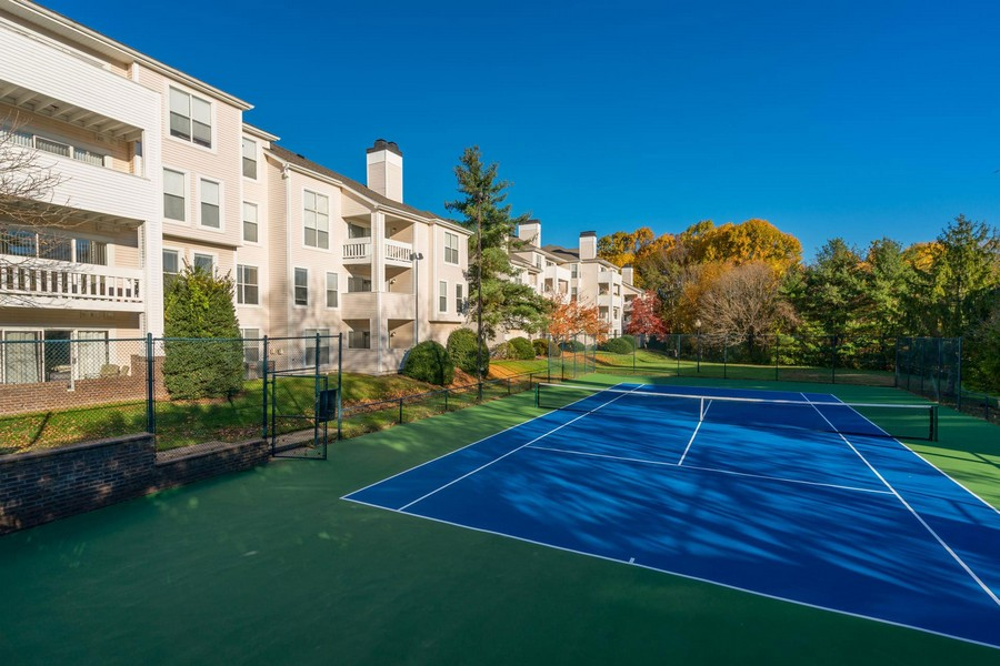 blue tennis courts, next to building, surrounded by trees, grass