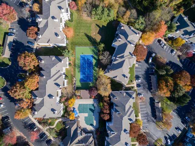 overhead shot of property, buildings, pool, tennis court, all surrounded by heavy treed area. Click to view the full size image.