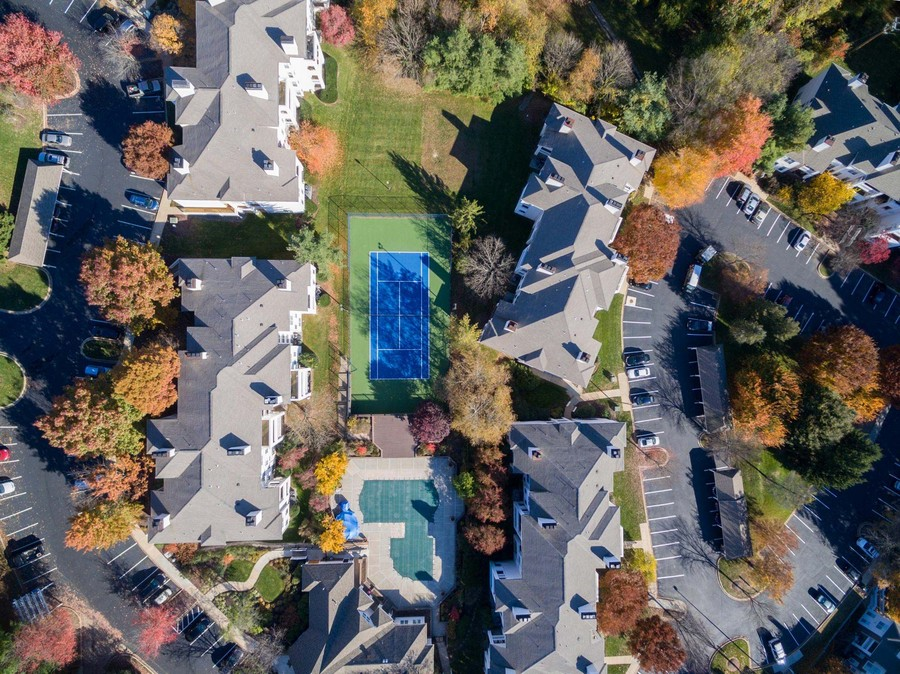 overhead shot of property, buildings, pool, tennis court, all surrounded by heavy treed area