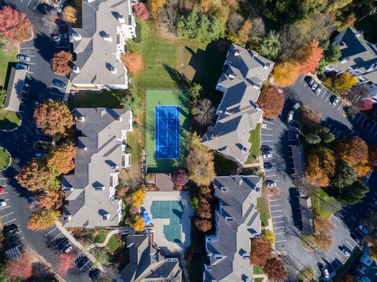 overhead shot of property, buildings, pool, tennis court, all surrounded by heavy treed area. Click to view the photo gallery.