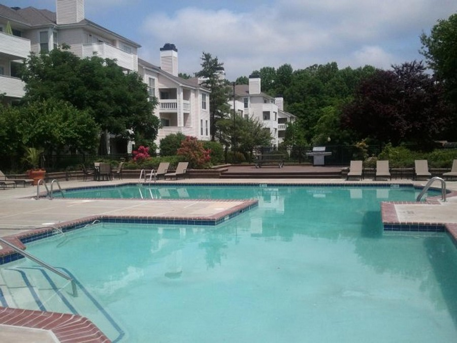 swimming pool near resident buildings, surrounded by trees