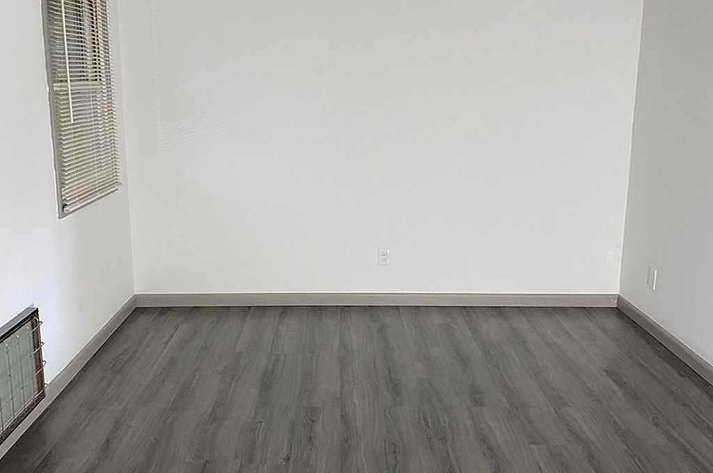 Main bedroom space with gray flooring