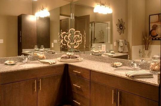 apartment bathroom with corner countertops and large mirrors