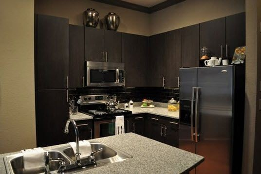 apartment kitchen with espresso cabinetry and stainless appliances