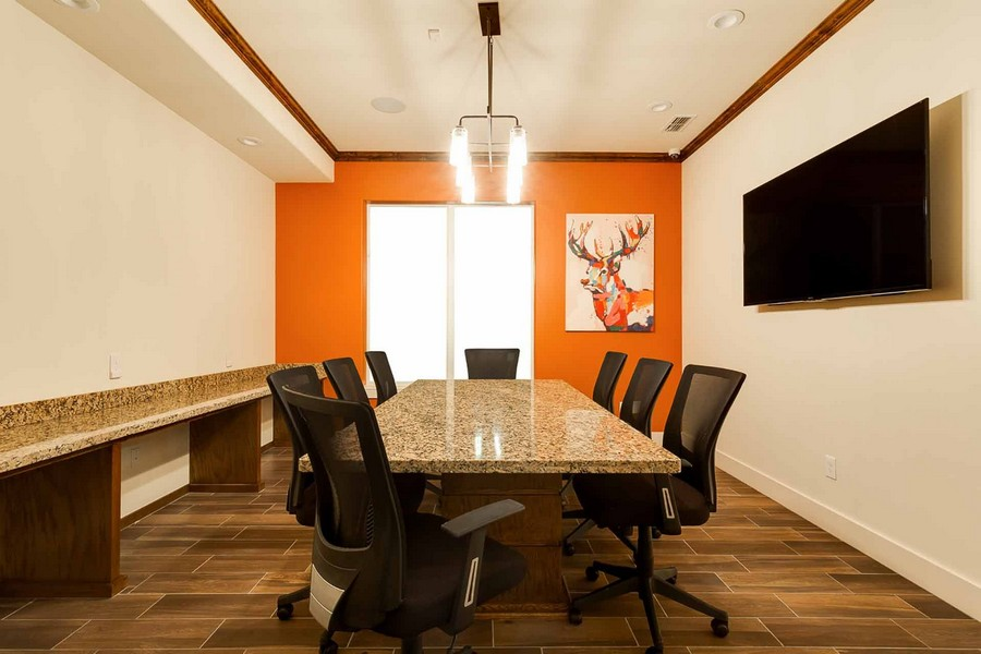 Business center with conference table, chairs, and TV