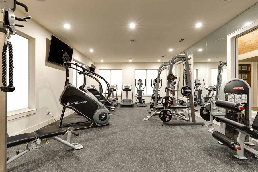 Fitness room with weights, stair machines, and treadmills
