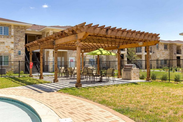 Outdoor semi-covered grilling area with two grills, tables, and chairs
